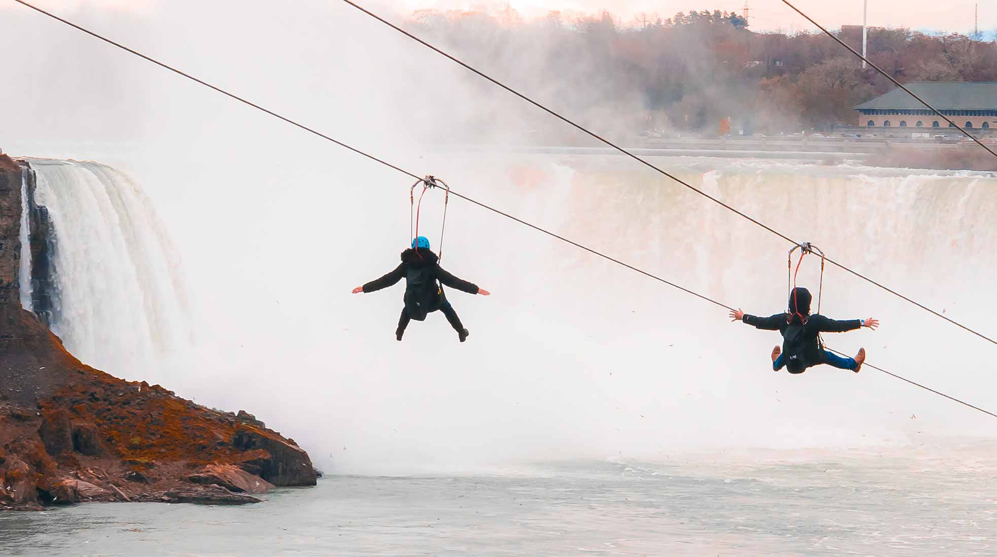 Two people riding a zipline over water towards a waterfall