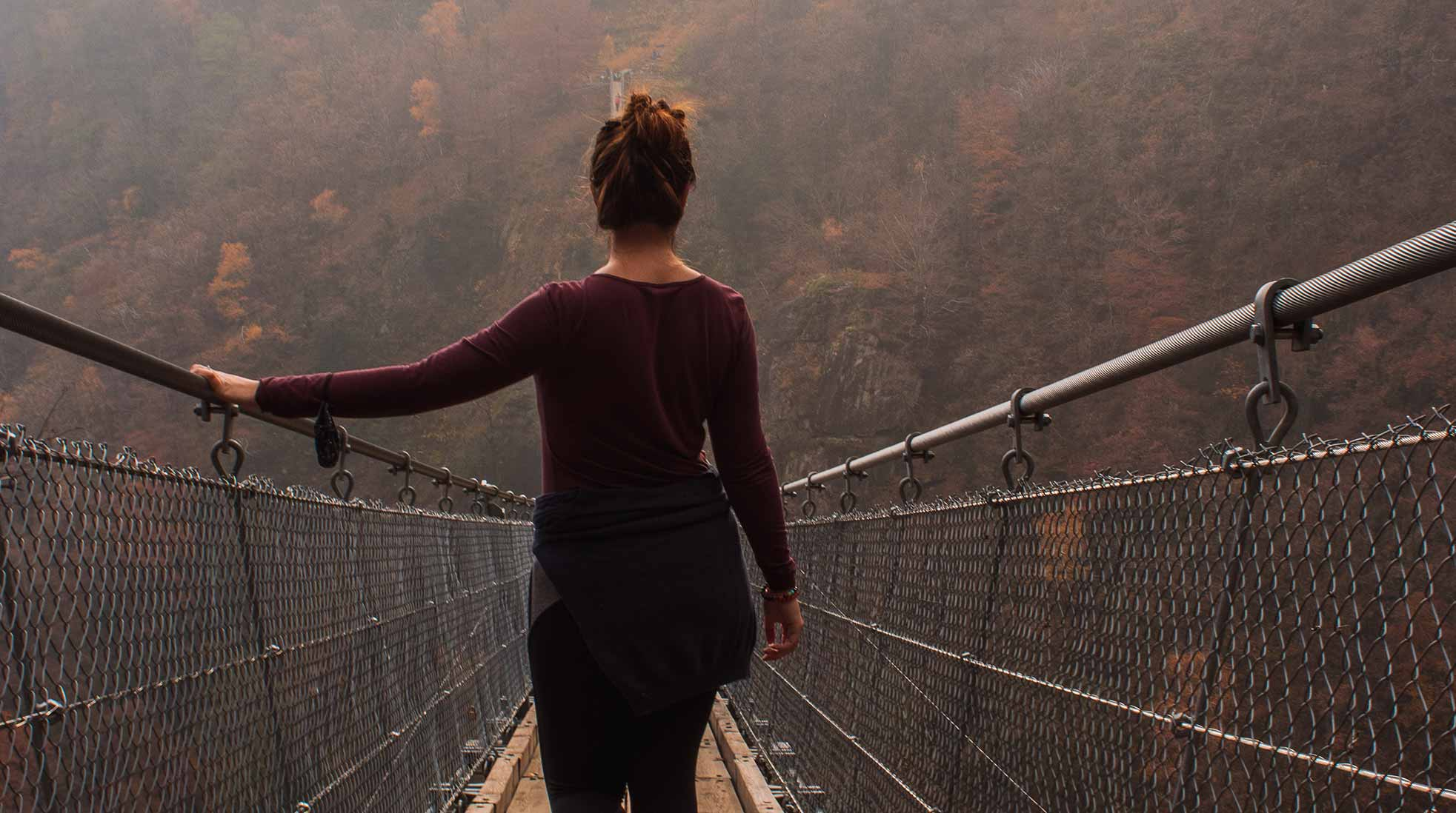 A woman walking a suspension bridge. Photo: Susanna Marsiglia / Unsplash