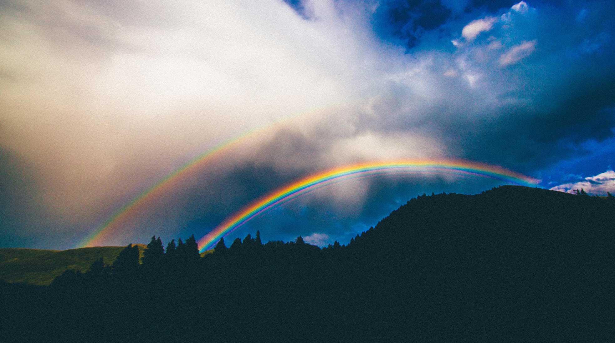 Double rainbow, cloudy skies