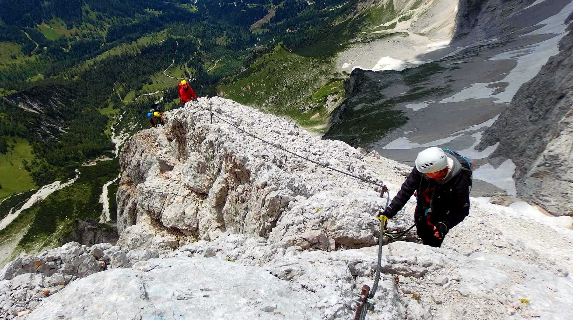 Three people climbing up a high mountain on a Via Ferrata