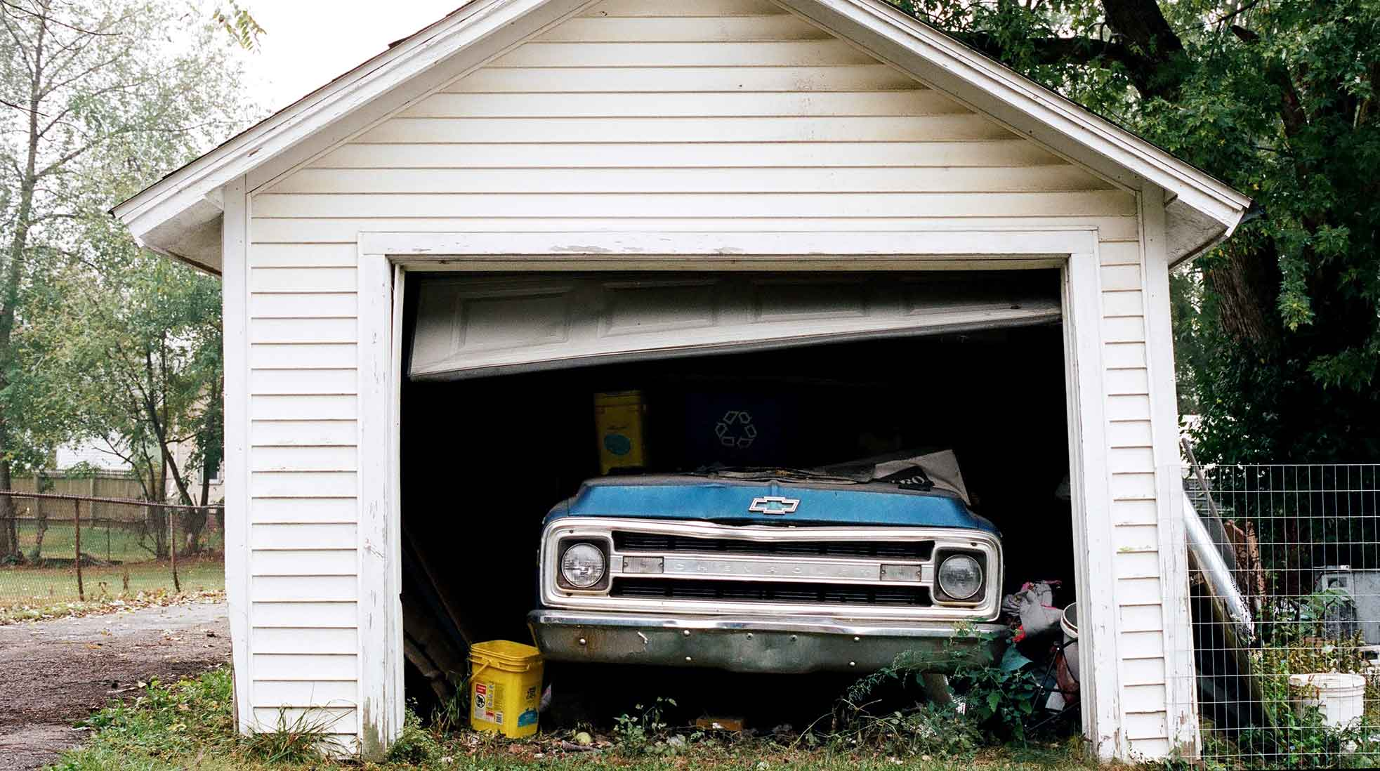 An old garage with a blue Chevrolet parked inside